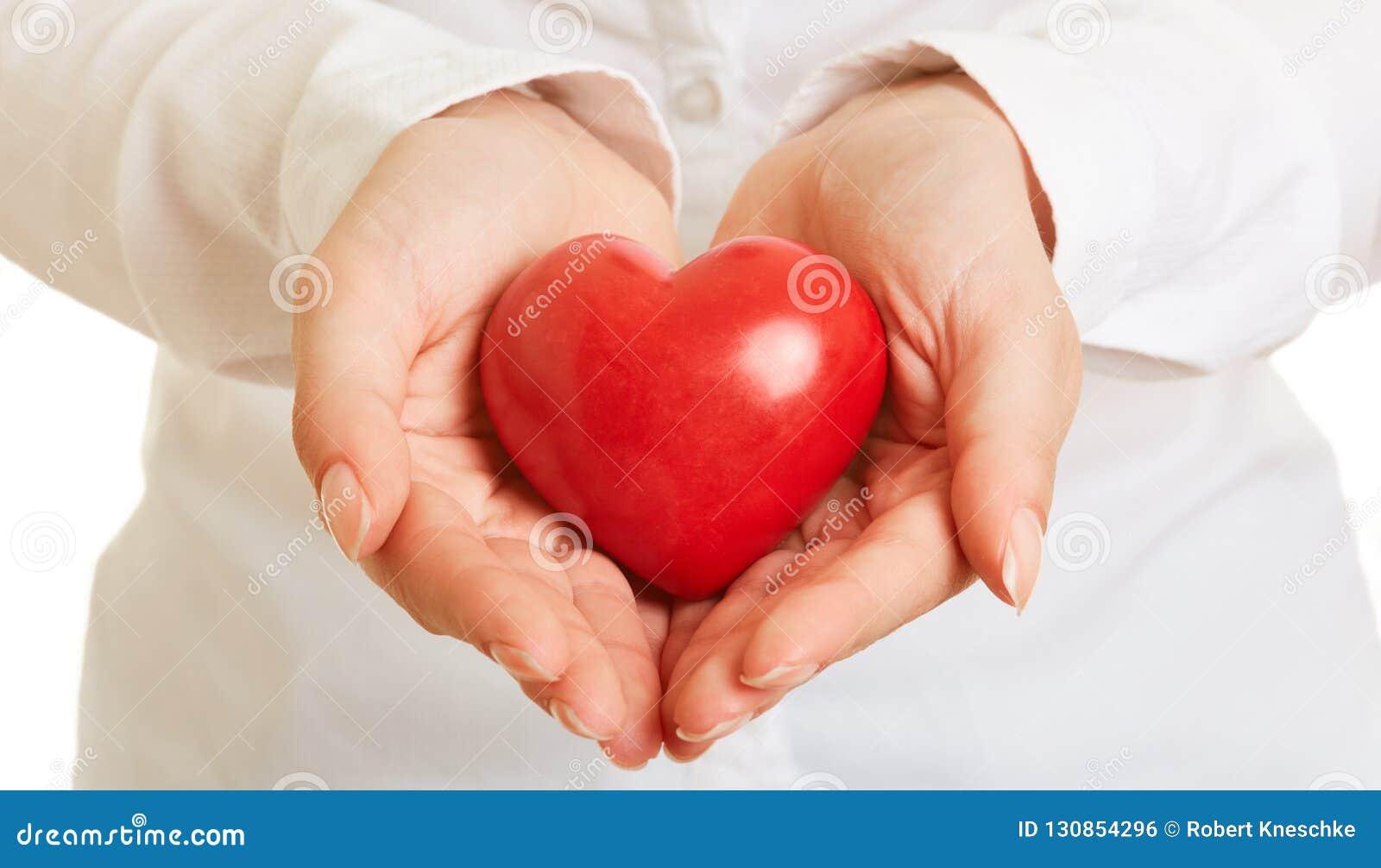 Händer rymmer hjärta som vård- försiktighetsbegrepp