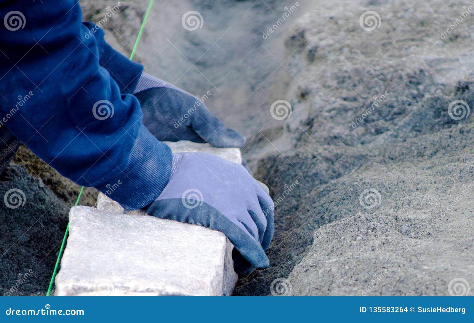Händer som förlägger kullersten på jordningen