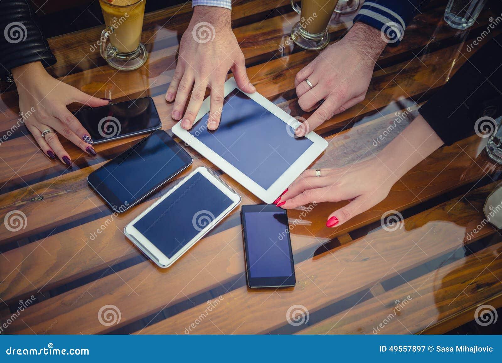 Händer som når för mobiltelefoner och minnestavla