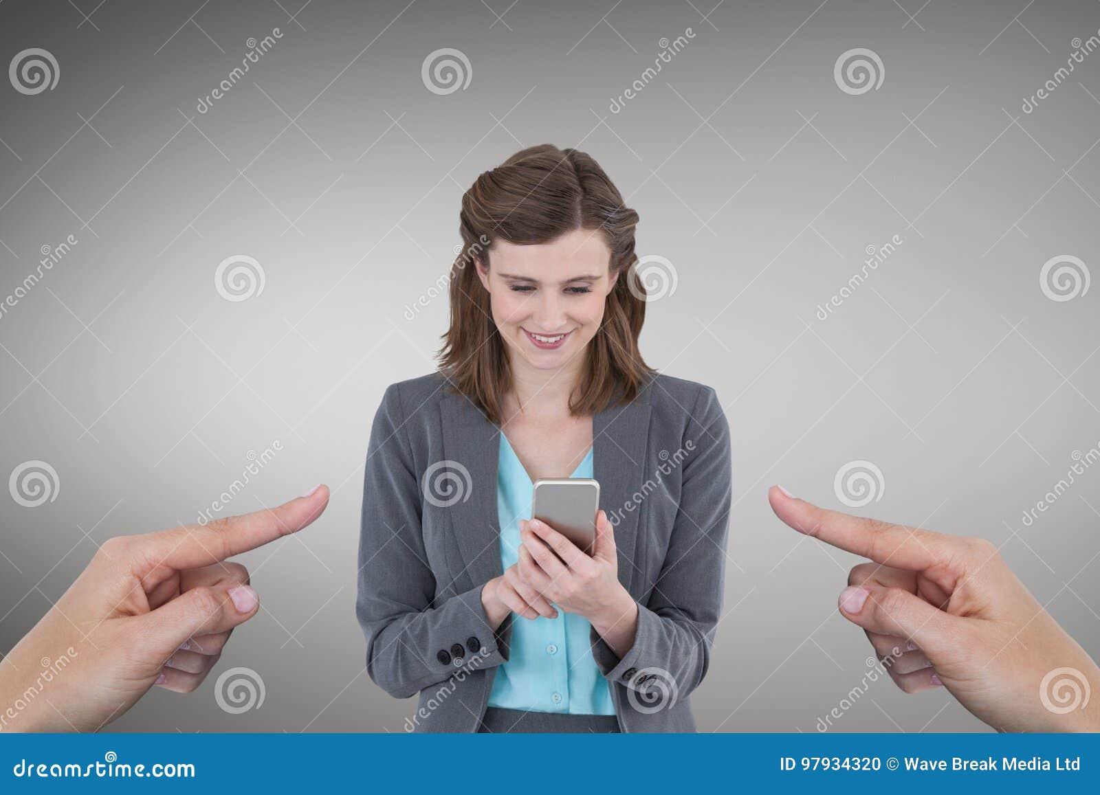 Händer som pekar på den lyckliga affärskvinnan som använder hennes telefon mot grå bakgrund