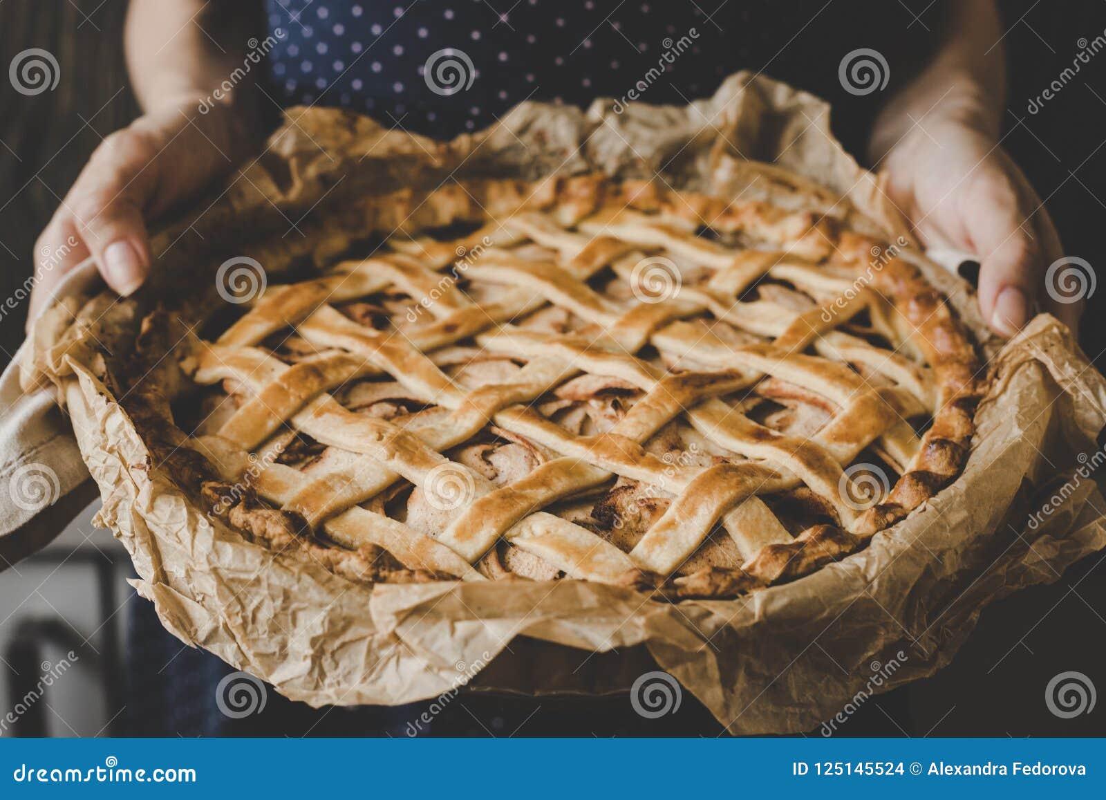 Händer som rymmer den hemlagade läckra äppelpajen close upp