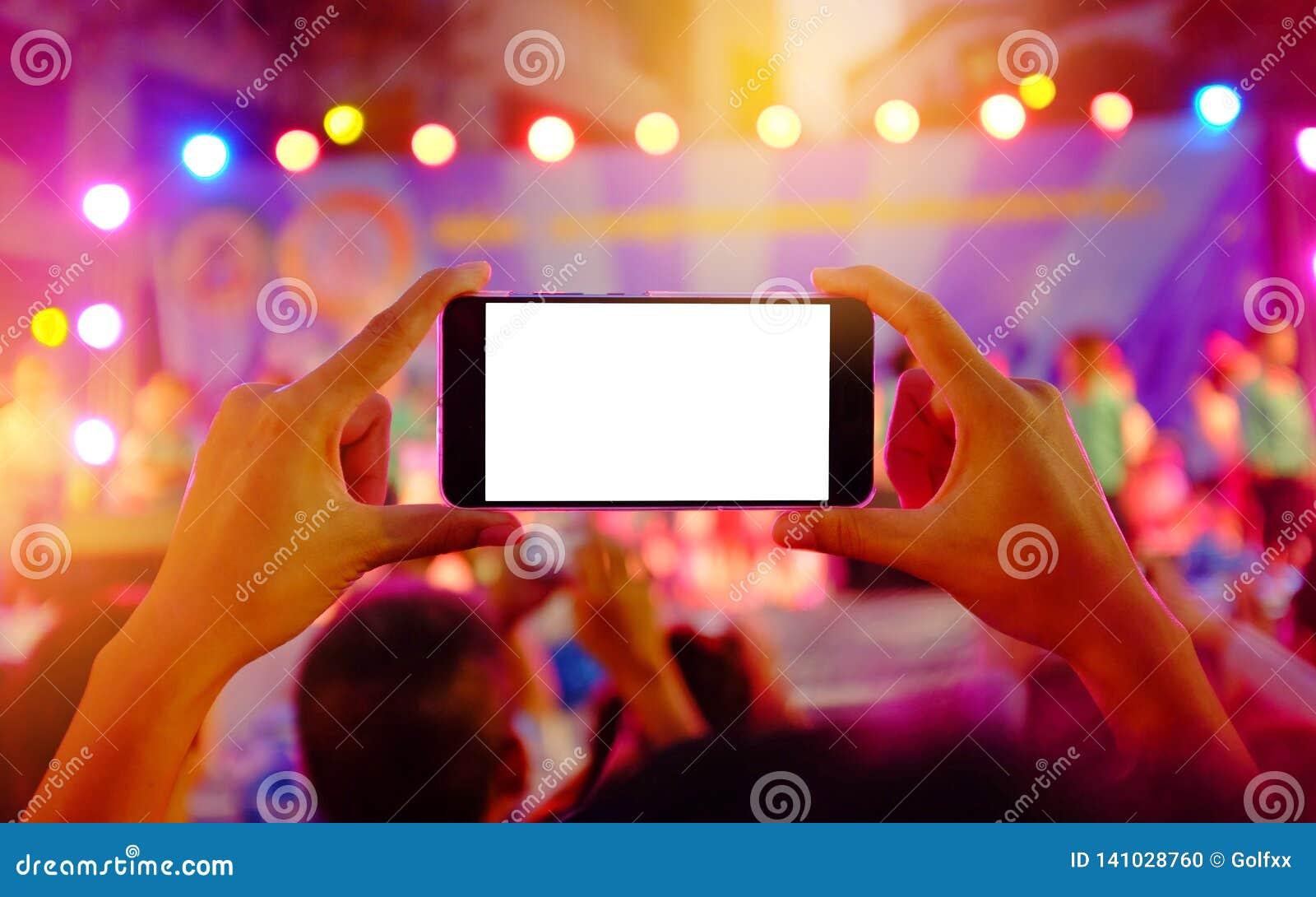 Händer som rymmer en mobil smartphone, antecknar färgrik levande konsert med den tomma vita skärmen