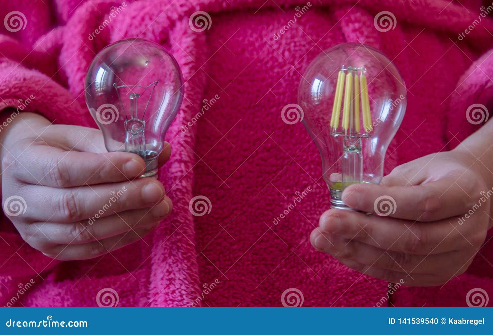 Händer som rymmer en ny ljus kula på ljusdioden och den glödande lampan Valet mellan ekonomi och effektivitet