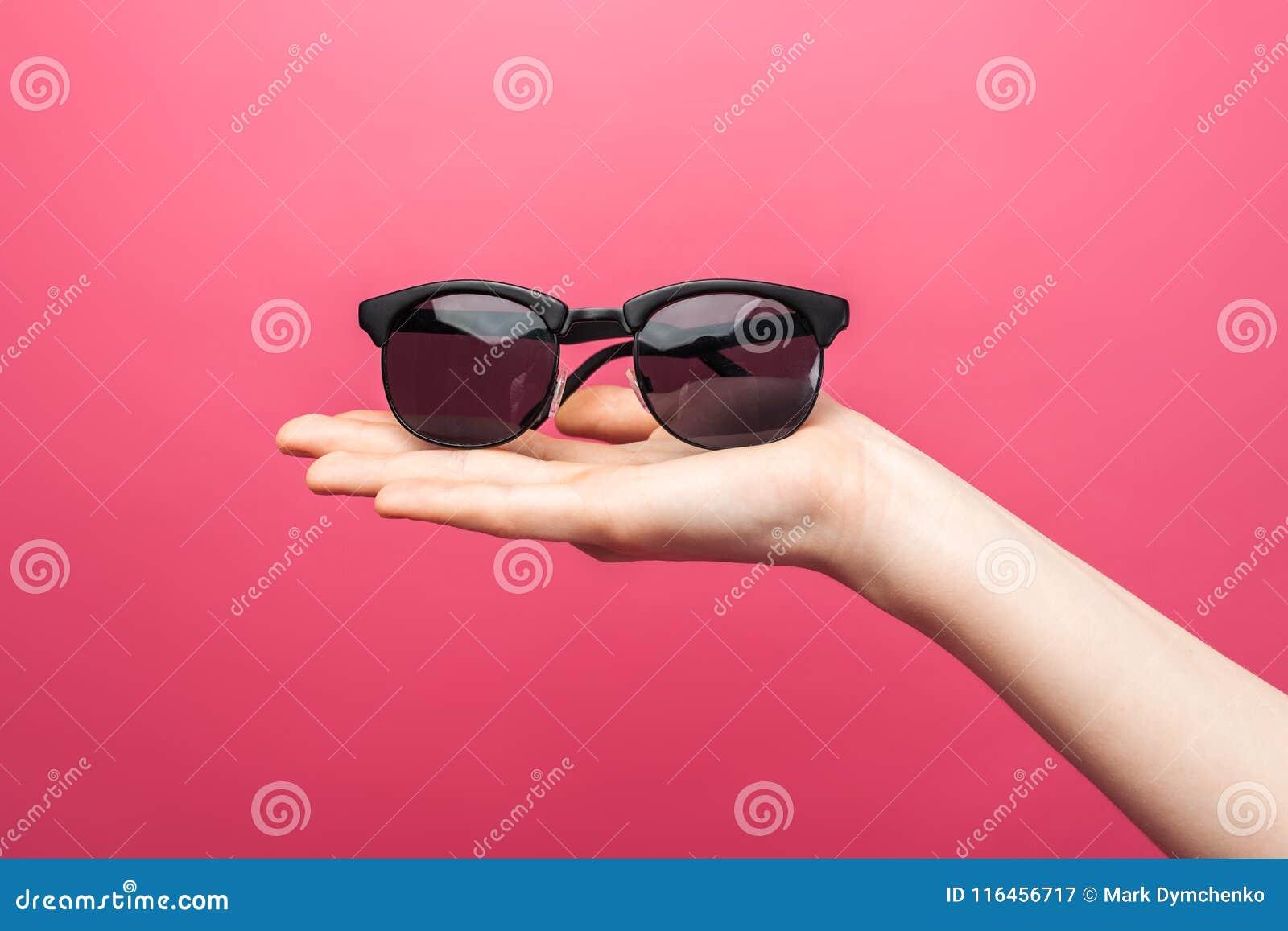 Händer som rymmer exponeringsglas, på rosa bakgrund som annonserar exponeringsglas, sommar, advertizingaffär