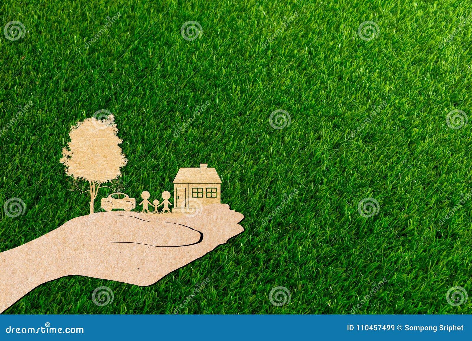 Händer som rymmer hem- stamträd- och bilgräsbakgrund