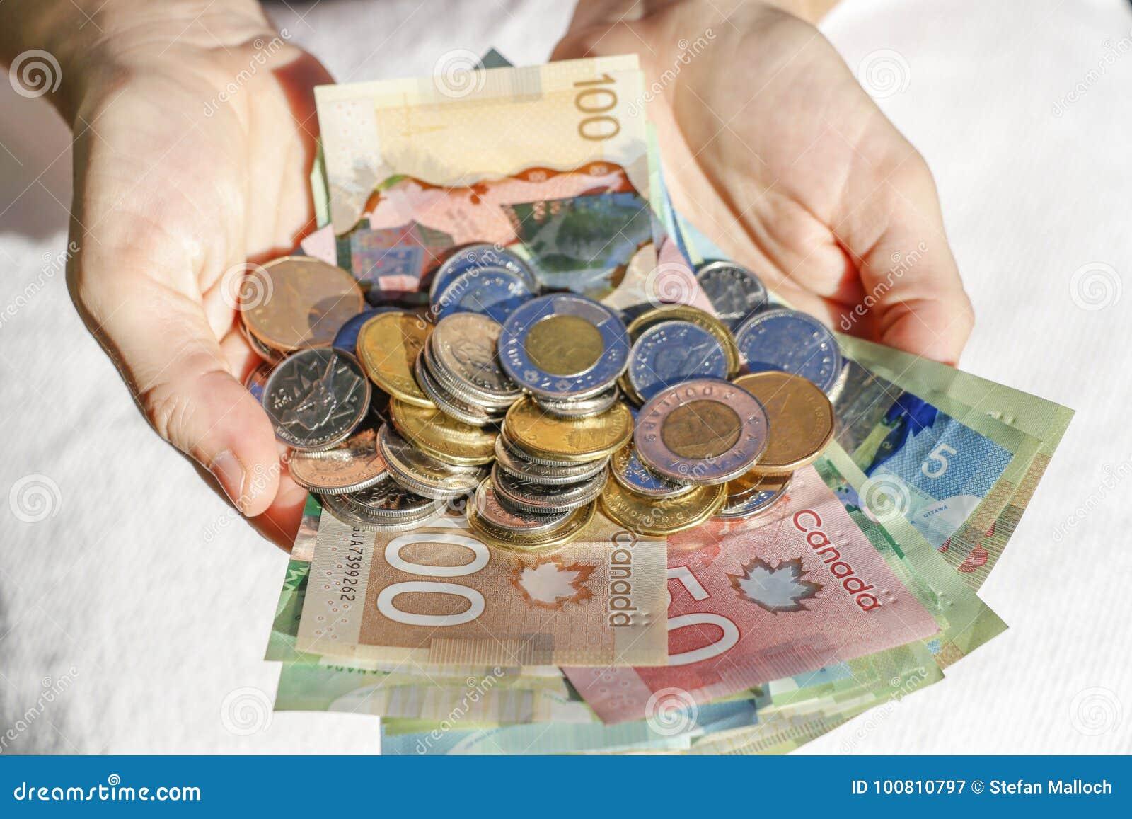 Händer som rymmer kanadensisk kassa och räkningar