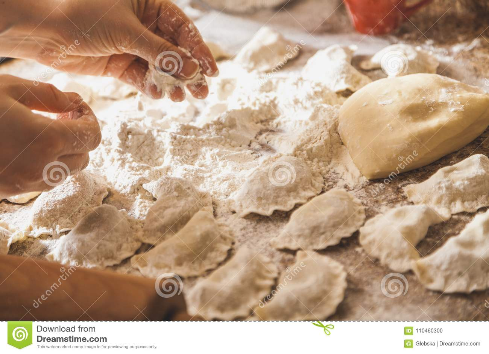 Händer strilar med rå klimpar för mjöl på tabellen