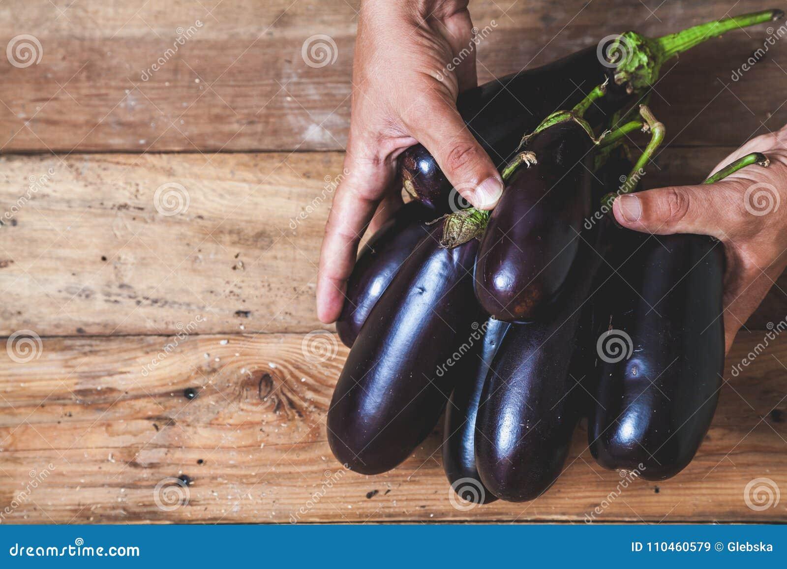 Händer tar få aubergine på träbräden