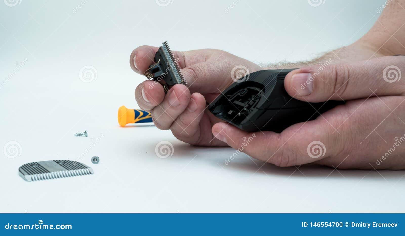 Händerna av män demonterade nagelsaxen och håret för maskinclipperreparation