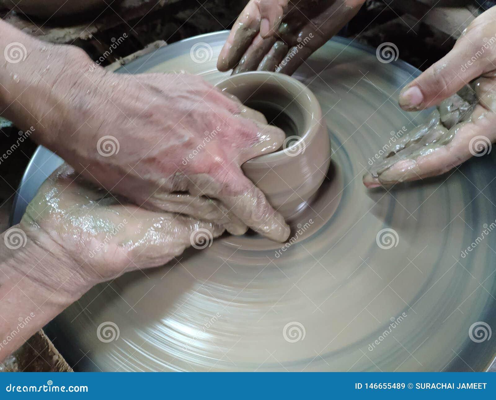 Händerna hugger leran in i den önskade formen r