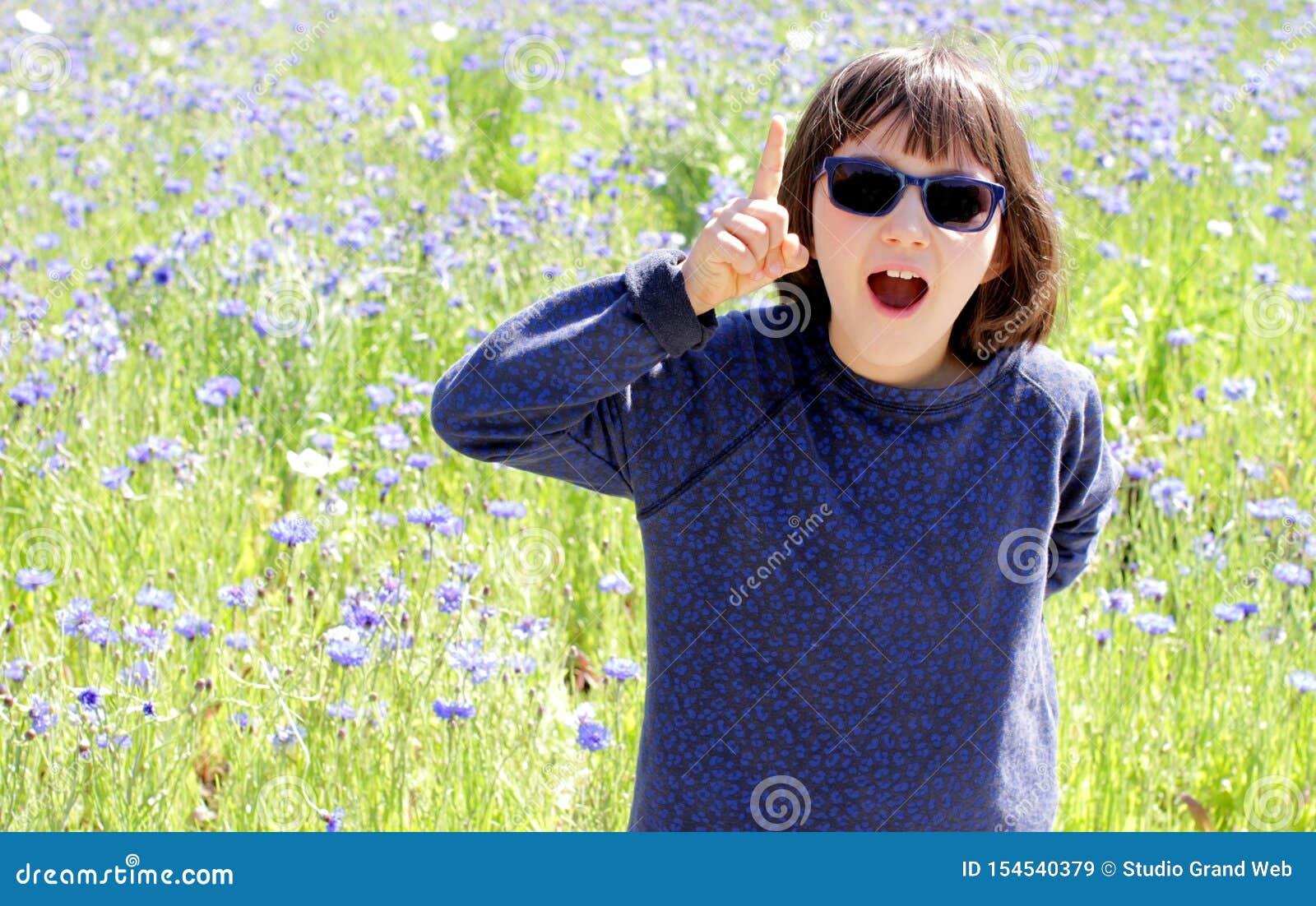 Hänfört uttrycksfullt barn med solglasögon över den soliga blåklintängen som är utomhus-
