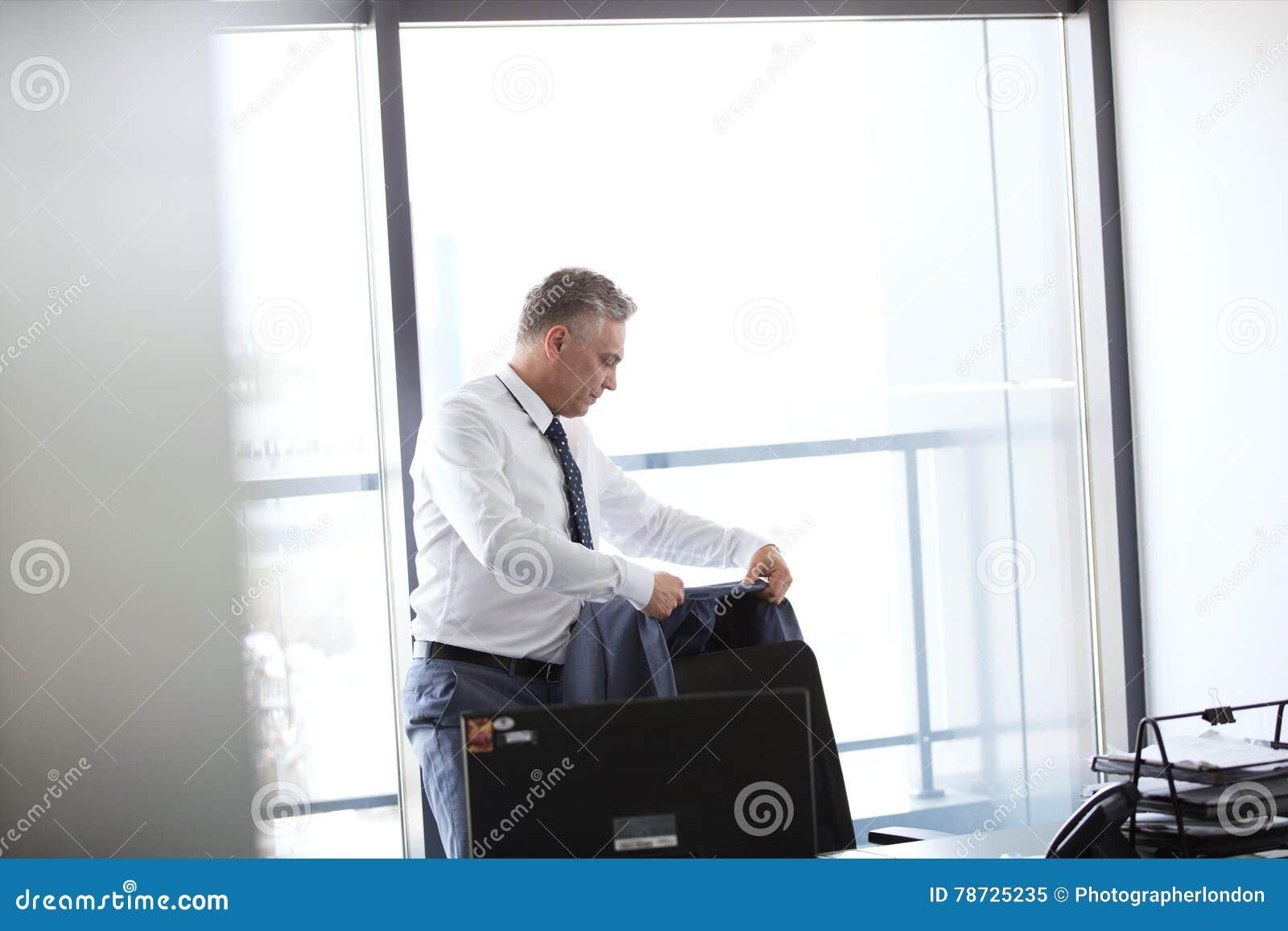 Hängande omslag för mogen affärsman på baksida av kontorsstol
