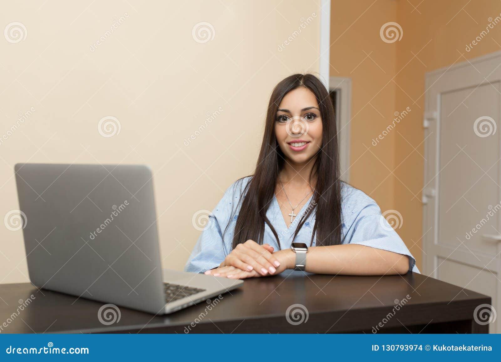 Härlig administratör för ung kvinna på mottagandet som arbetar på bärbara datorn