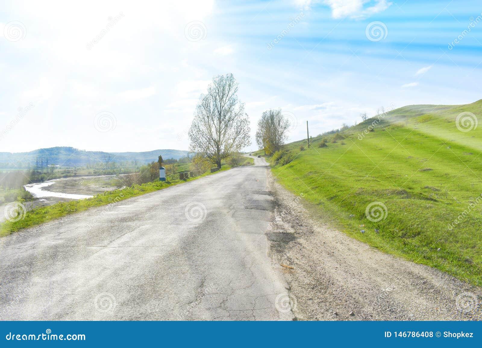 Härlig asfalterad väg på den stora gröna kullen i en solig sommardag