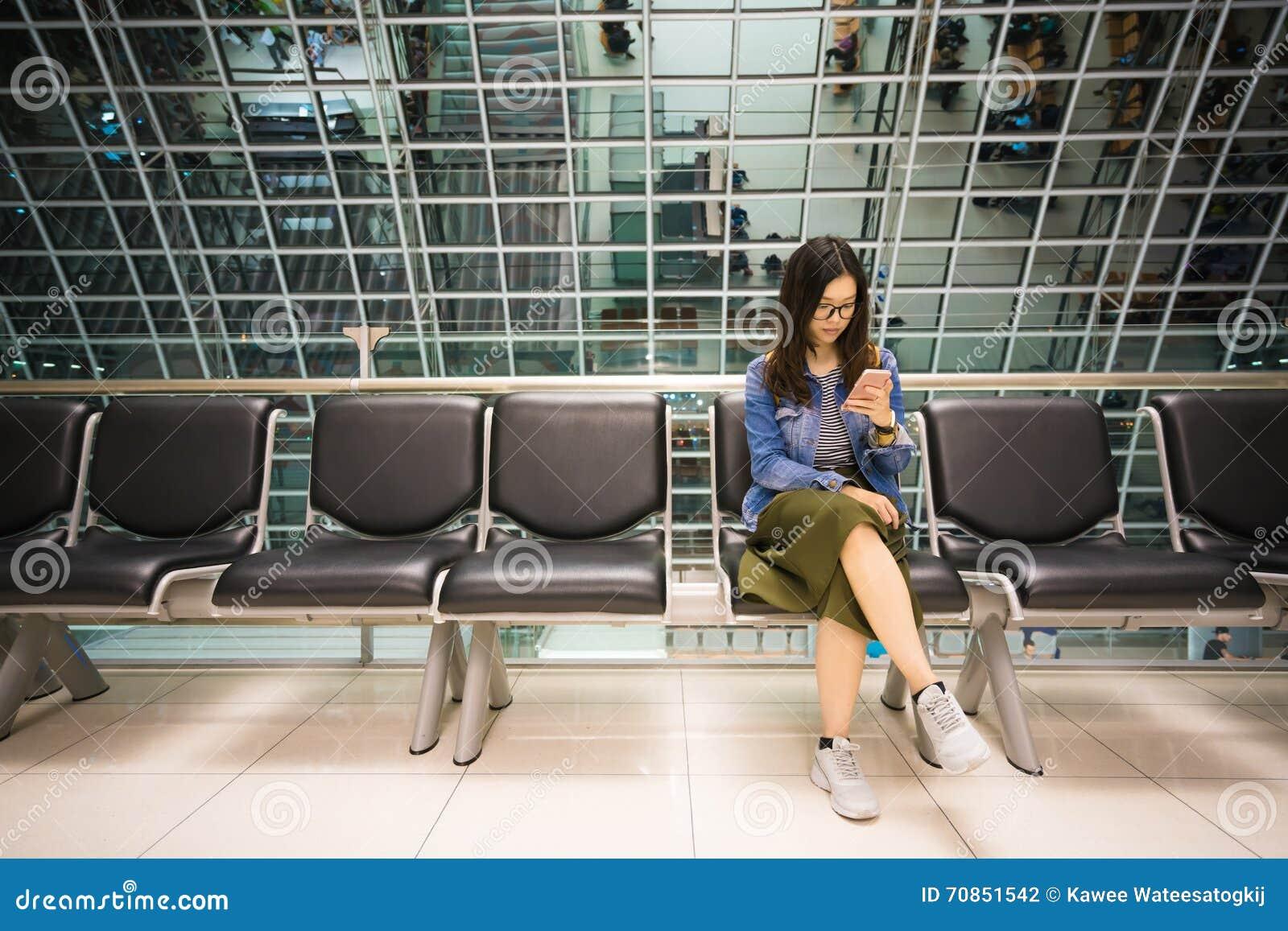 Härlig asiatisk flicka som använder smartphonen som väntar för att stiga ombord flygplanet som är begreppsmässigt