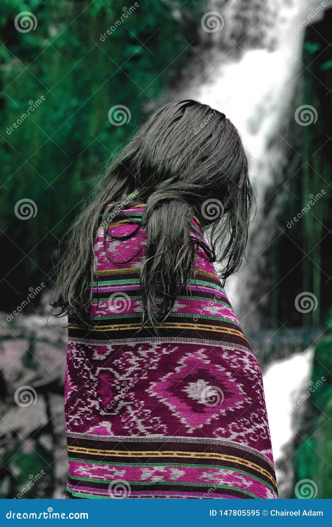 Härlig asiatisk flickastående i den purpurfärgade filten som är främst av den härliga naturliga vattenfallet och grön skog