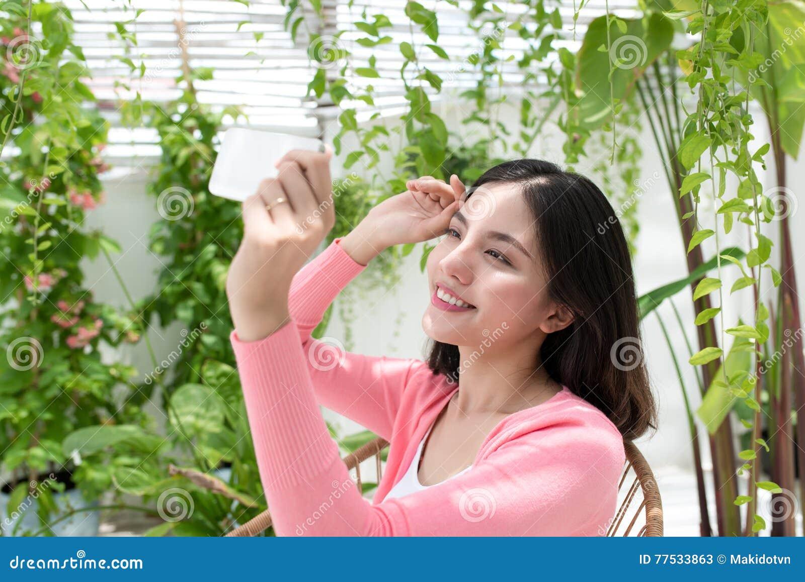 Härlig asiatisk ung kvinna som hemma kopplar av och använder mobiltelefonen på balkong