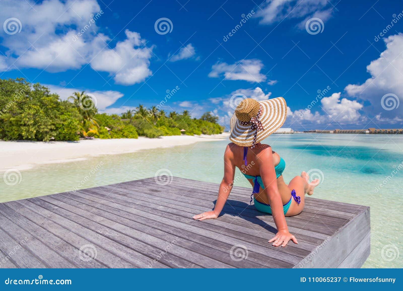 Härlig attraktiv kvinna i bikinin och hatten som ligger på strandträbryggan och den lyxiga vattenvillan Havssikt, lyxig livsstil