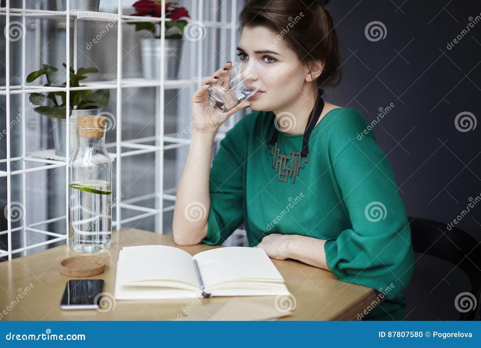 Härlig bärande gräsplan för den unga kvinnan som dricker rent vatten i kafé och att ha frukosten, öppnade bokspridning på tabelle