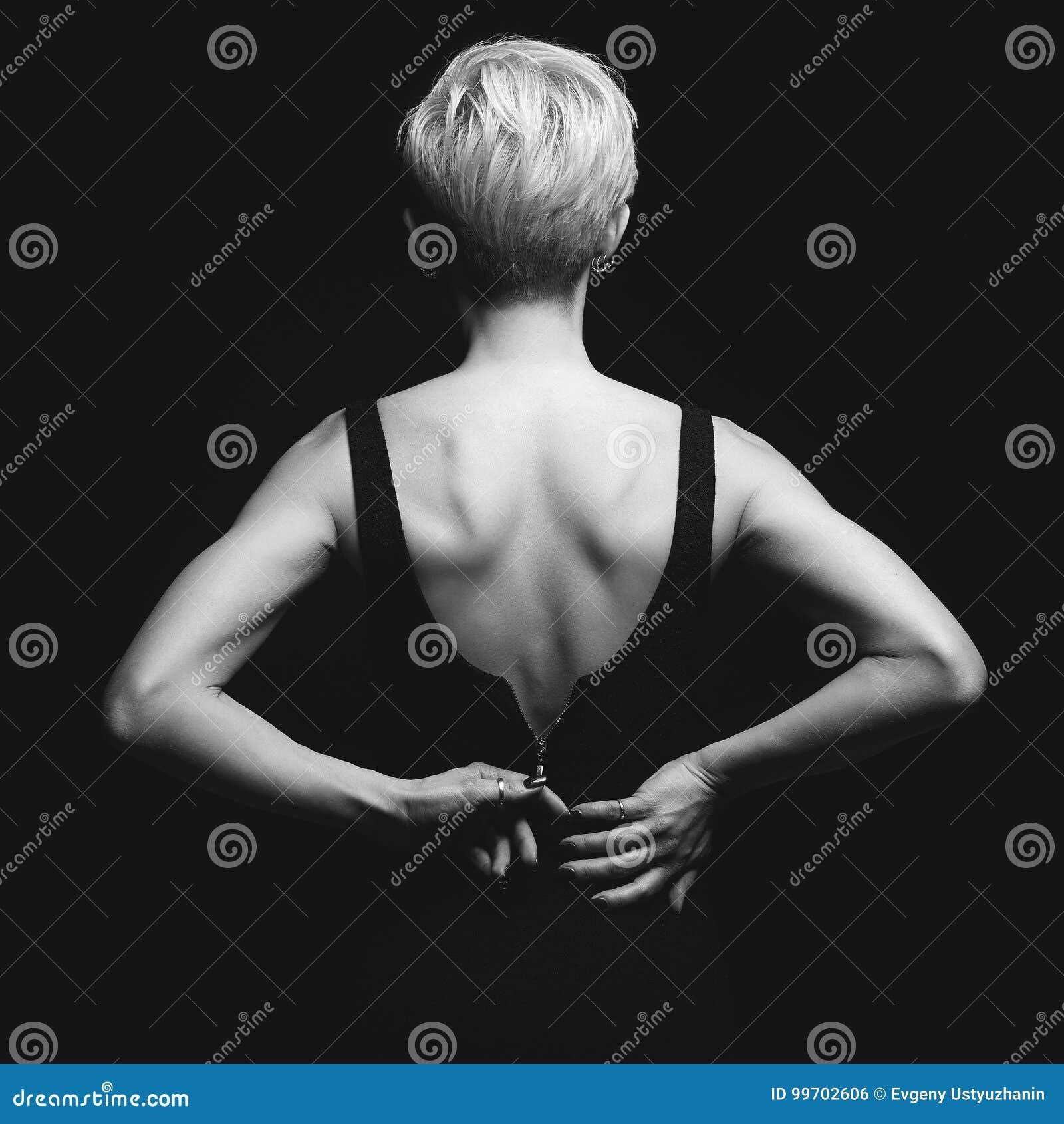 Härlig baksida av den unga kvinnan i en svart sexig klänning