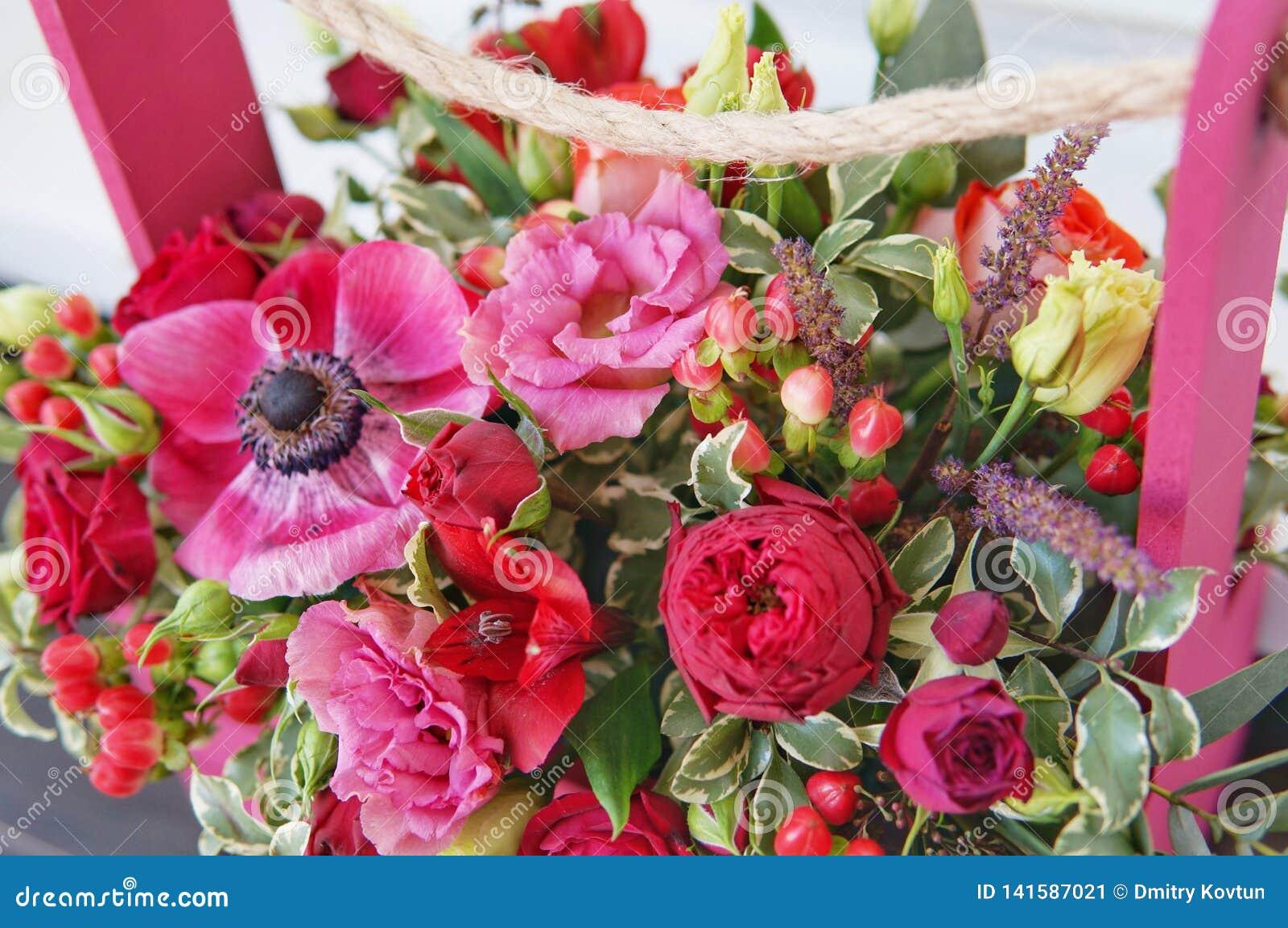 Härlig blom- ordning av röda, rosa och burgundy blommor i en rosa träask