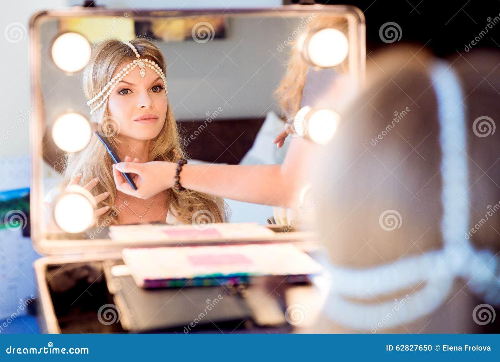 Härlig blond brud som gör makeup i hennes bröllopdag nära mirro