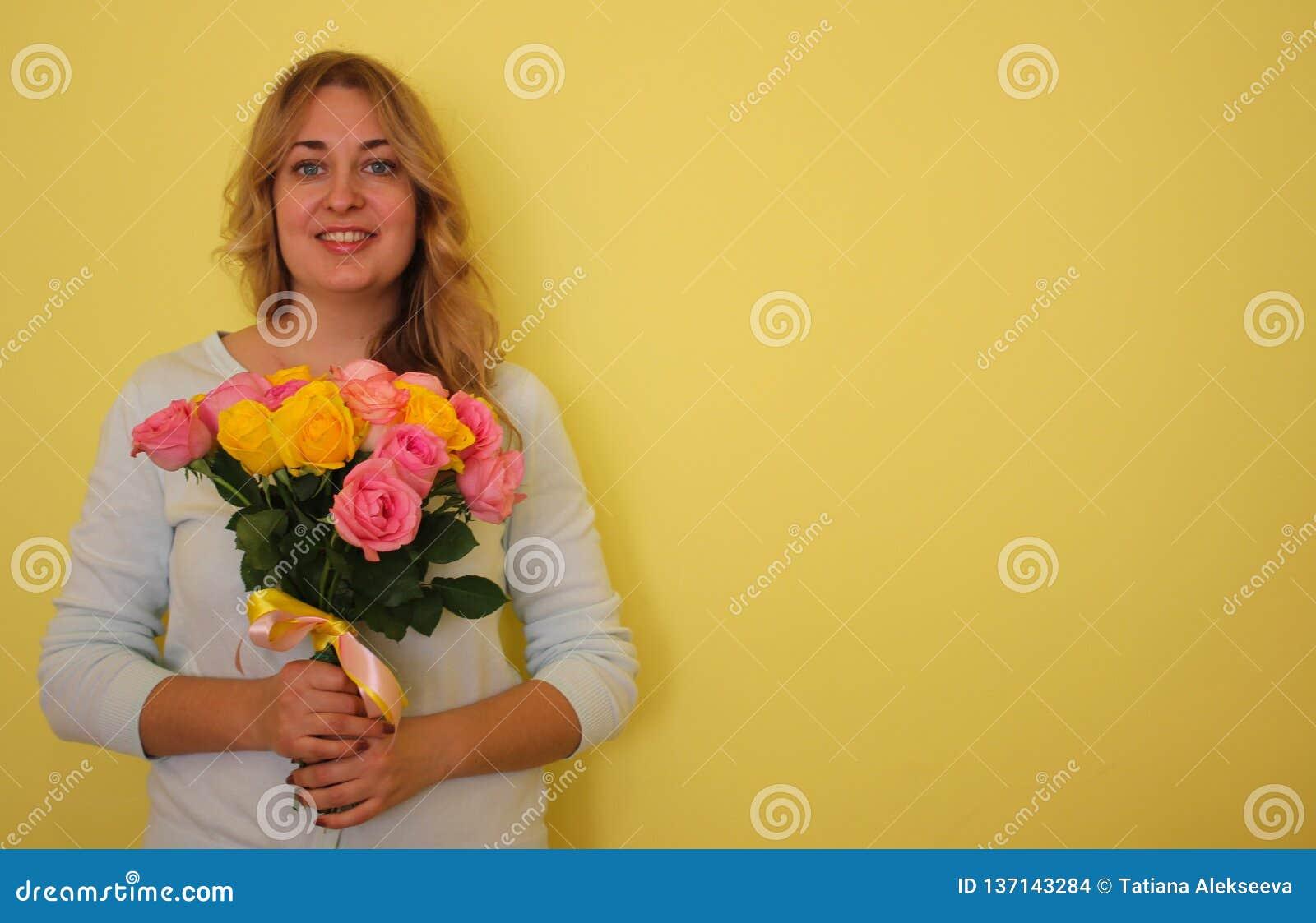 Härlig blond flicka i den blåa klänninginnehavbuketten av gula och rosa rosor på enguling bakgrund
