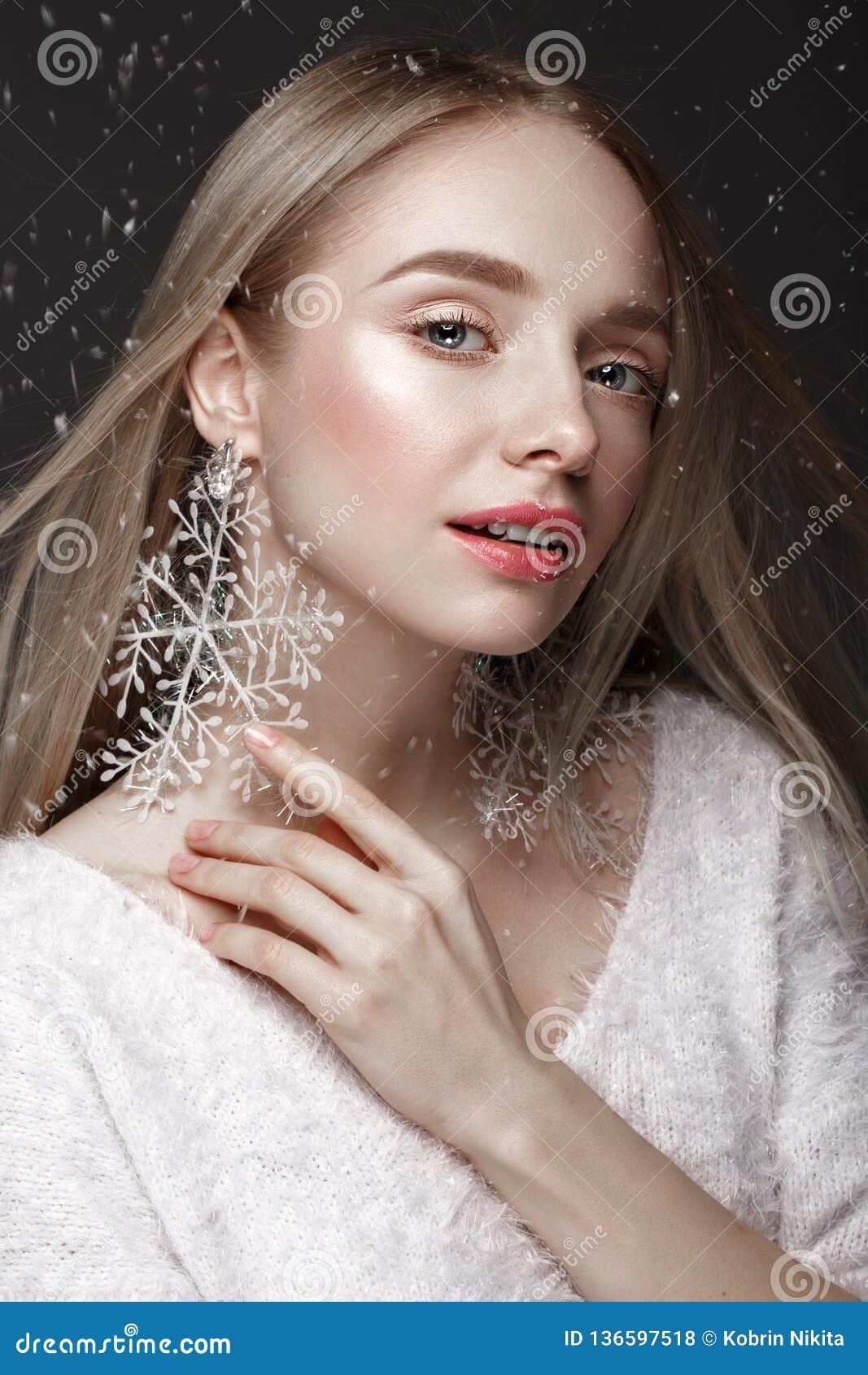 Härlig blond flicka i en vinterbild med snö Härlig le flicka