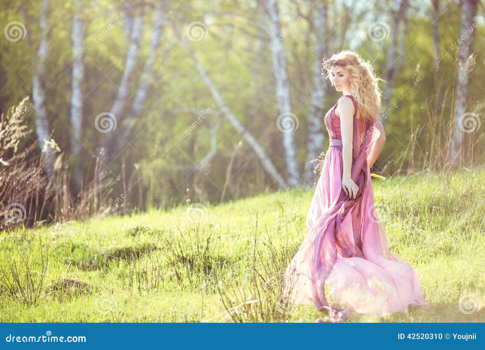 Härlig blond flicka i rosa lång klänning på en bakgrund av naturen