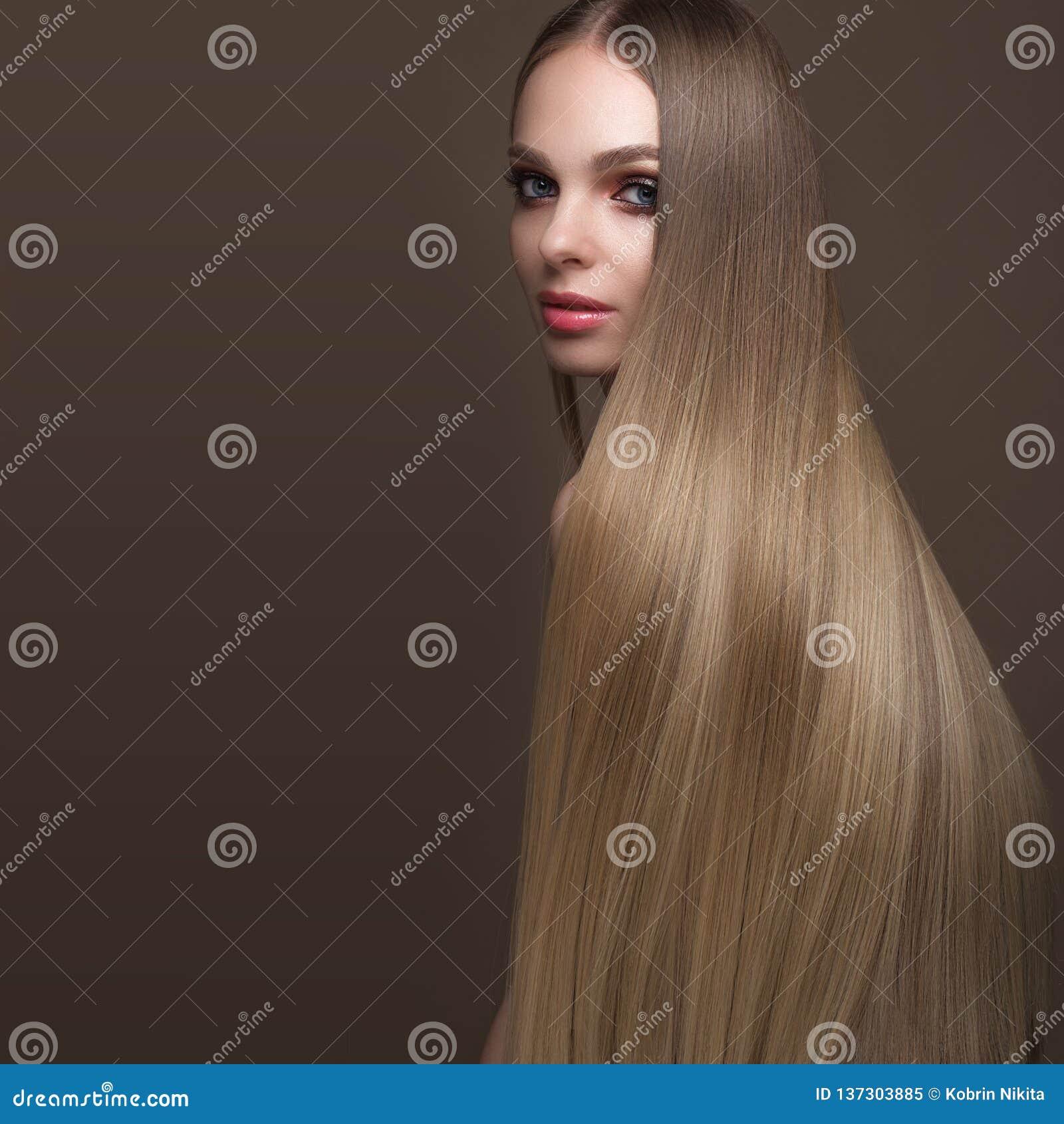 Härlig blond flicka med ett perfekt slätt hår, klassiskt smink Härlig le flicka