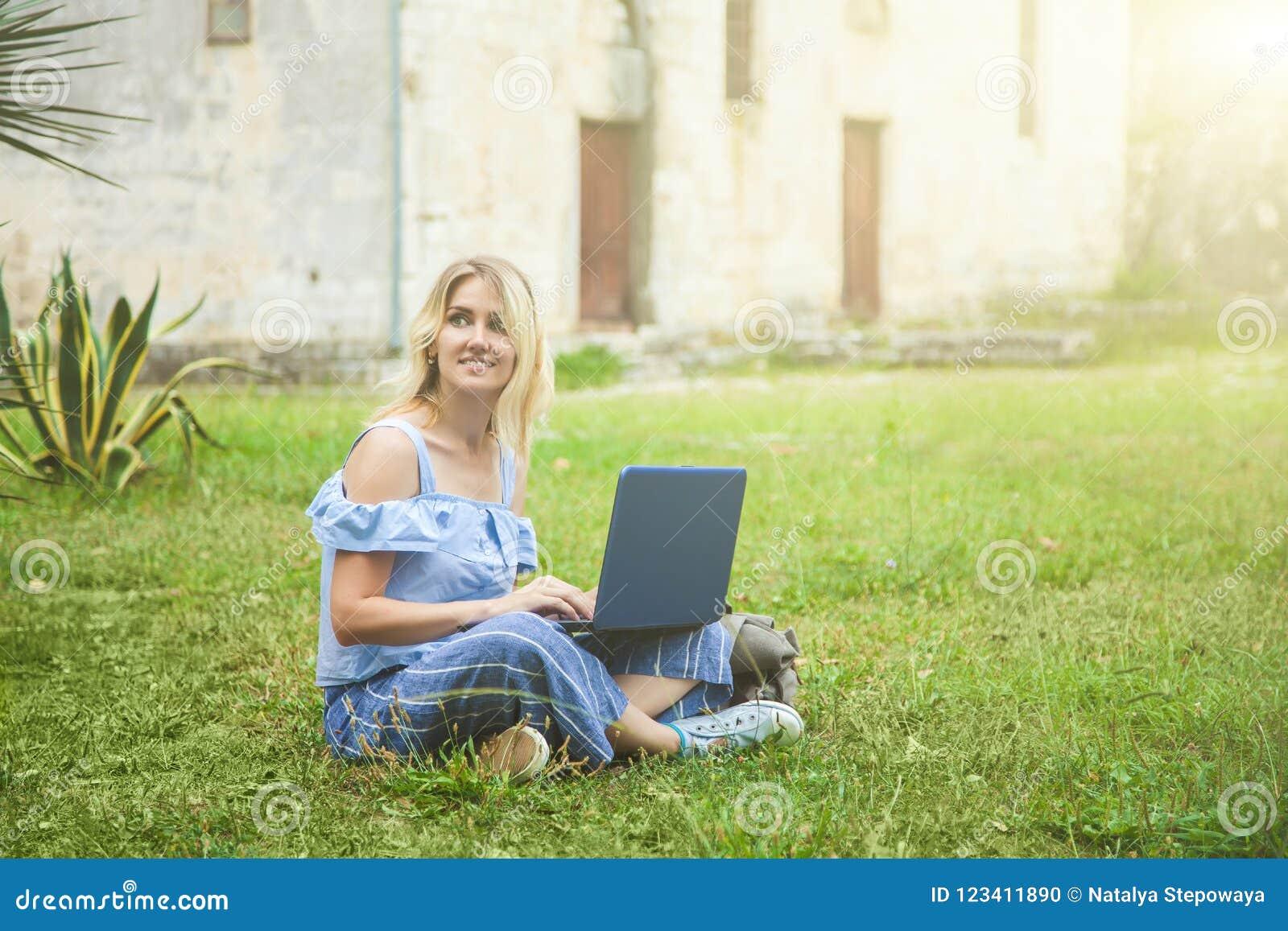 Härlig blond flicka som arbetar på en bärbar dator i parkera