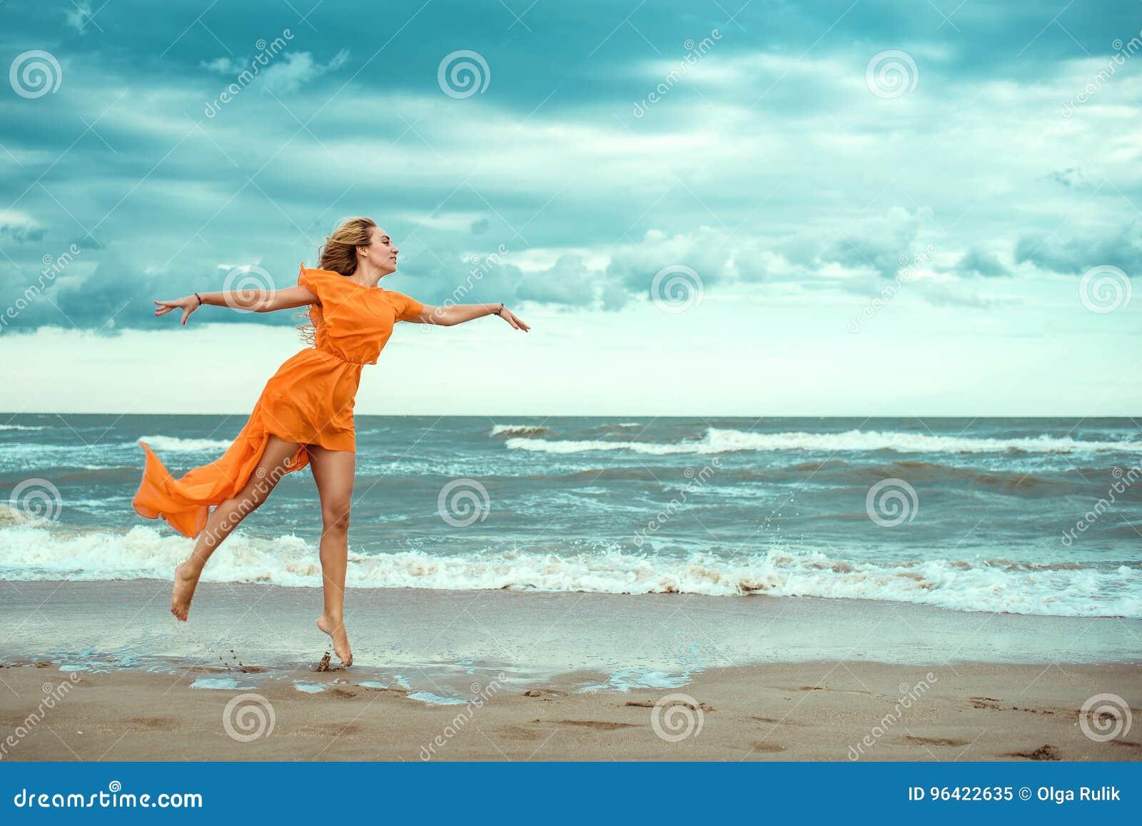 Härlig blond kvinna i orange mini- klänning med flygdrevet som barfota dansar på den våta sanden på det fantastiska havet