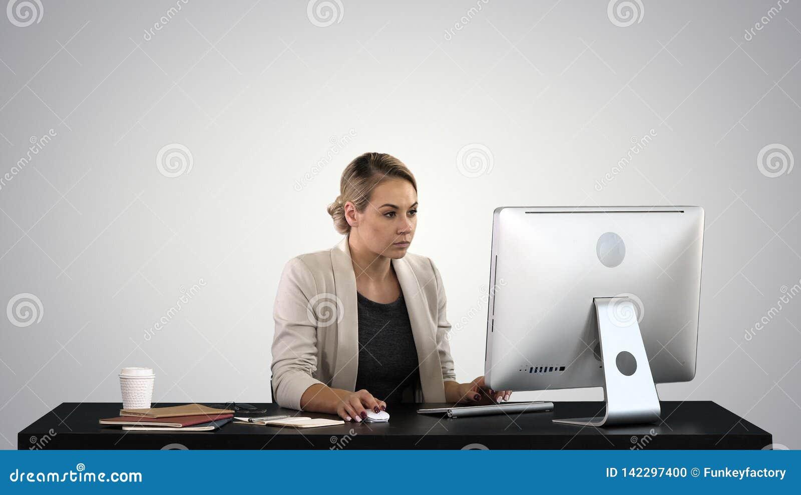 Härlig blond kvinna som arbetar på datoren på lutningbakgrund