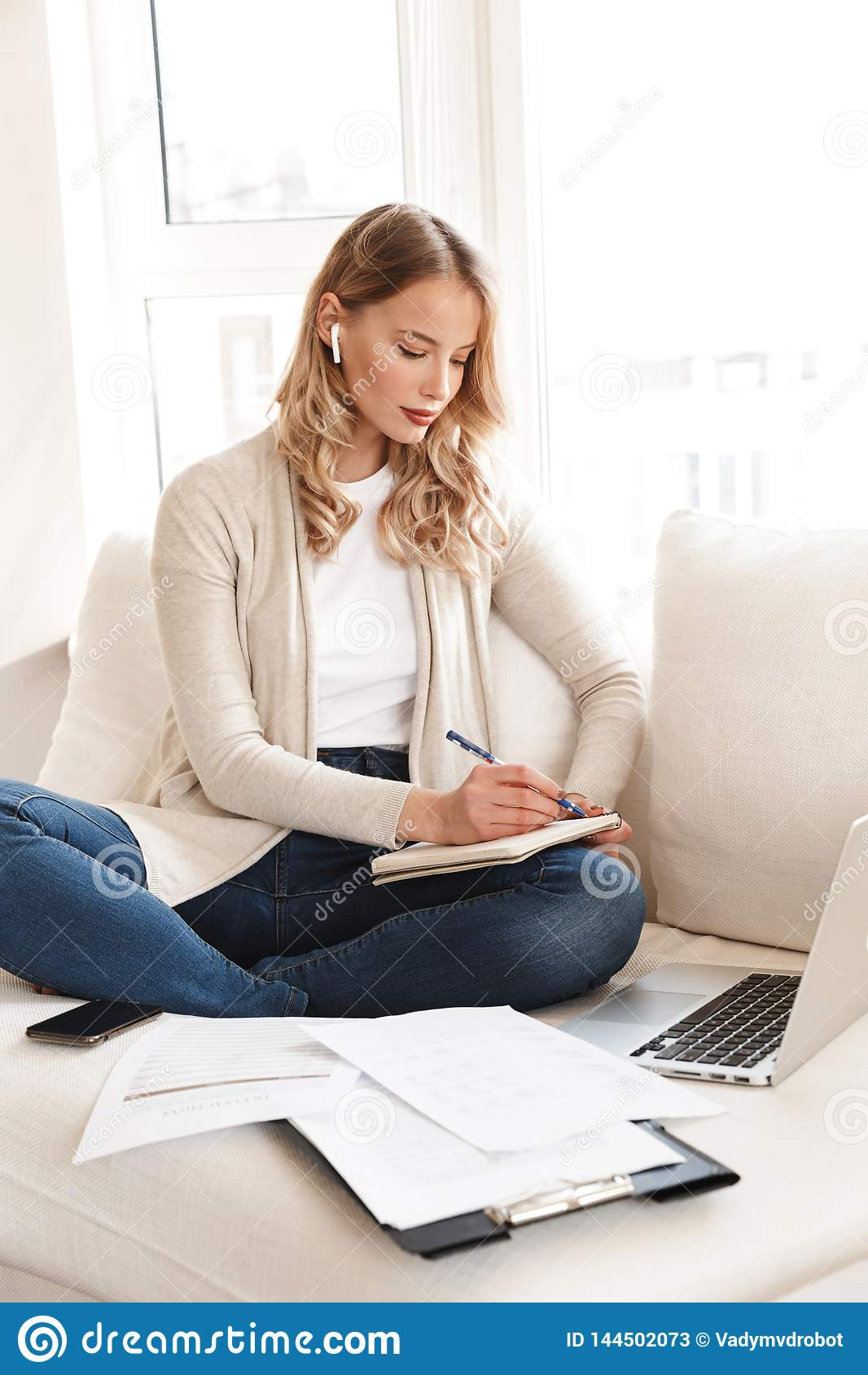 Härlig blond kvinna som poserar att sitta inomhus hemma genom att använda anmärkningar för handstil för bärbar datordator
