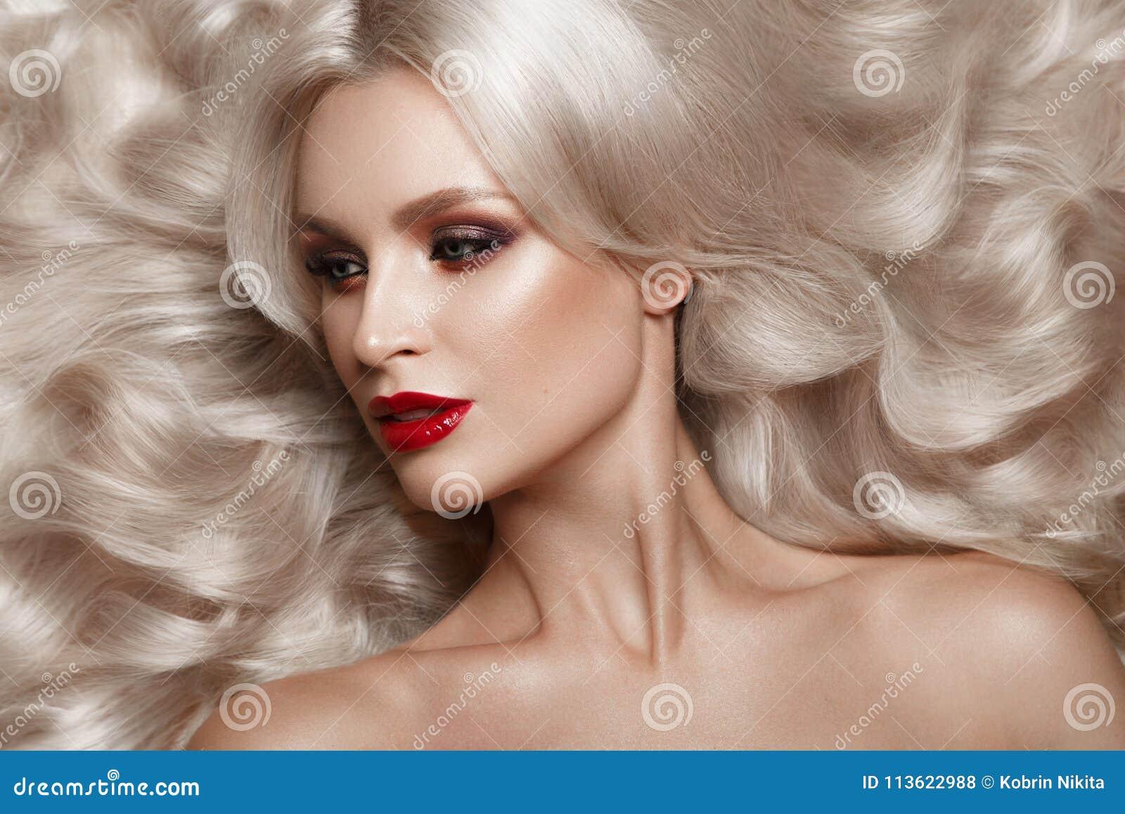 Härlig blondin i ett Hollywood sätt med krullning, naturlig makeup och röda kanter Skönhetframsida och hår
