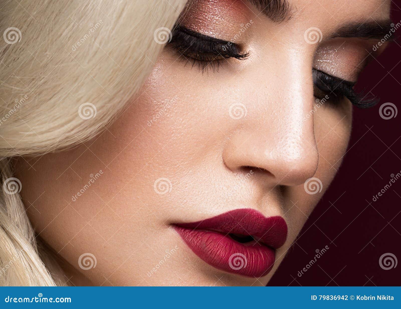 Härlig blondin i ett Hollywood sätt med krullning, röda kanter Skönhetframsida och hår