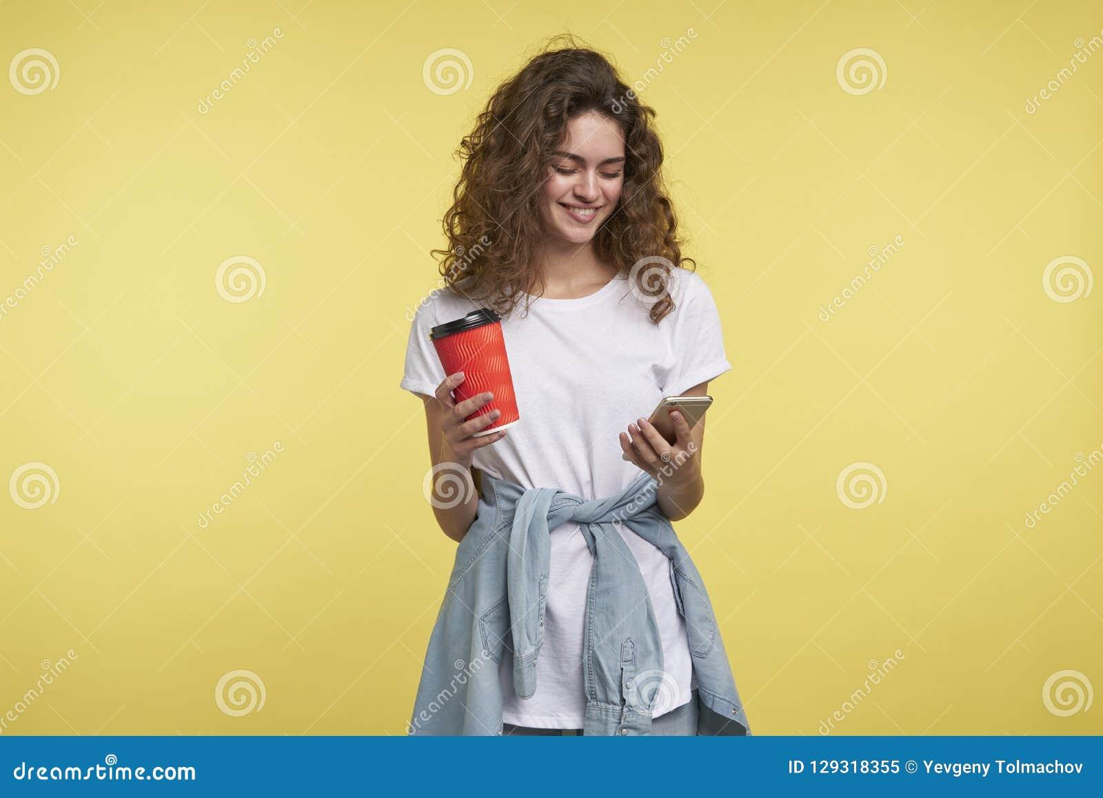 Härlig blyg brunettkvinna som pratar via whatsappbudbärare henne som rymmer kaffekoppen, ett skott som isoleras över guling