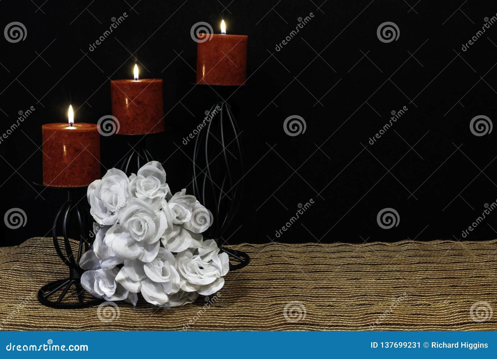 Härlig bouquie av vita rosor, röda stearinljus som sätta sig på svarta stearinljushållare på den matta för ingreppsställe och trä