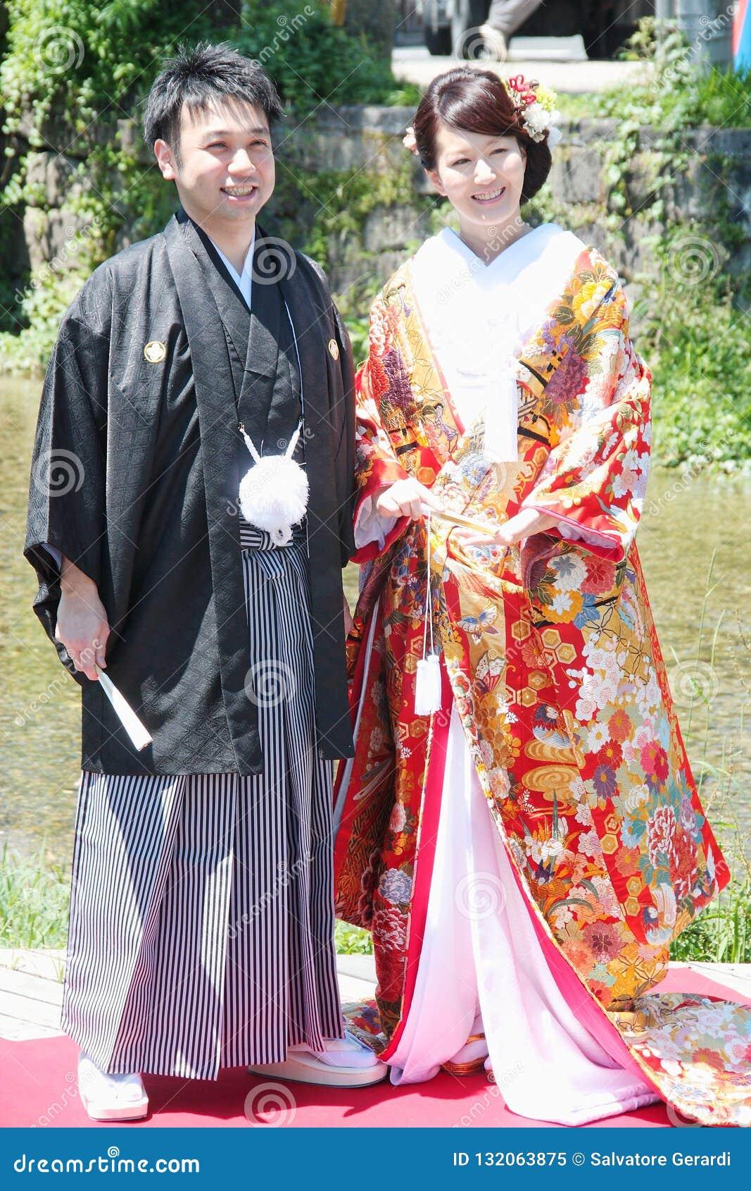 Härlig brud och brudgum som bär den traditionella japanska bröllopsklänningen i Kyoto Japan
