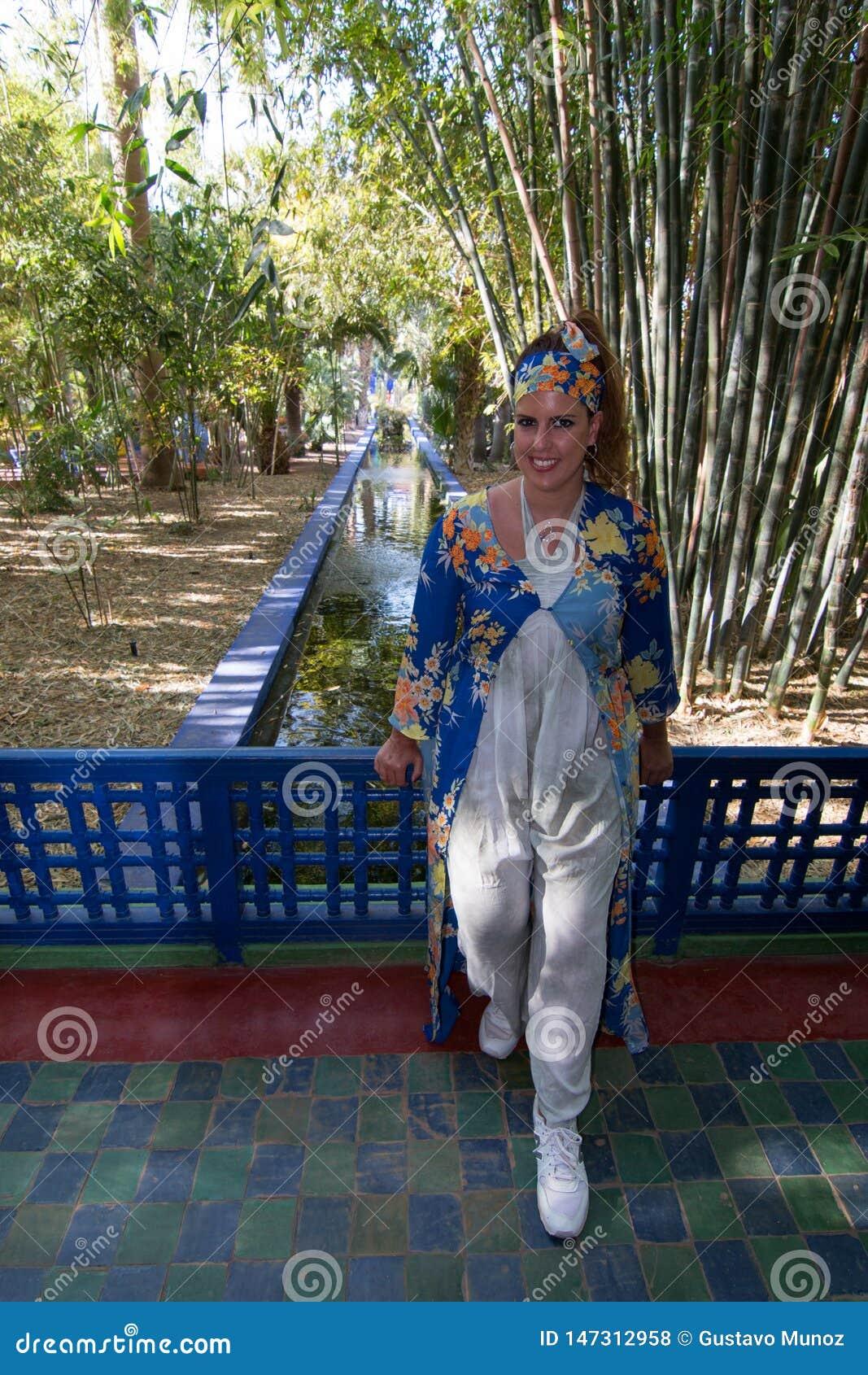 Härlig brunettkvinnastående med en mycket färgrik etnisk klänning i en trädgård