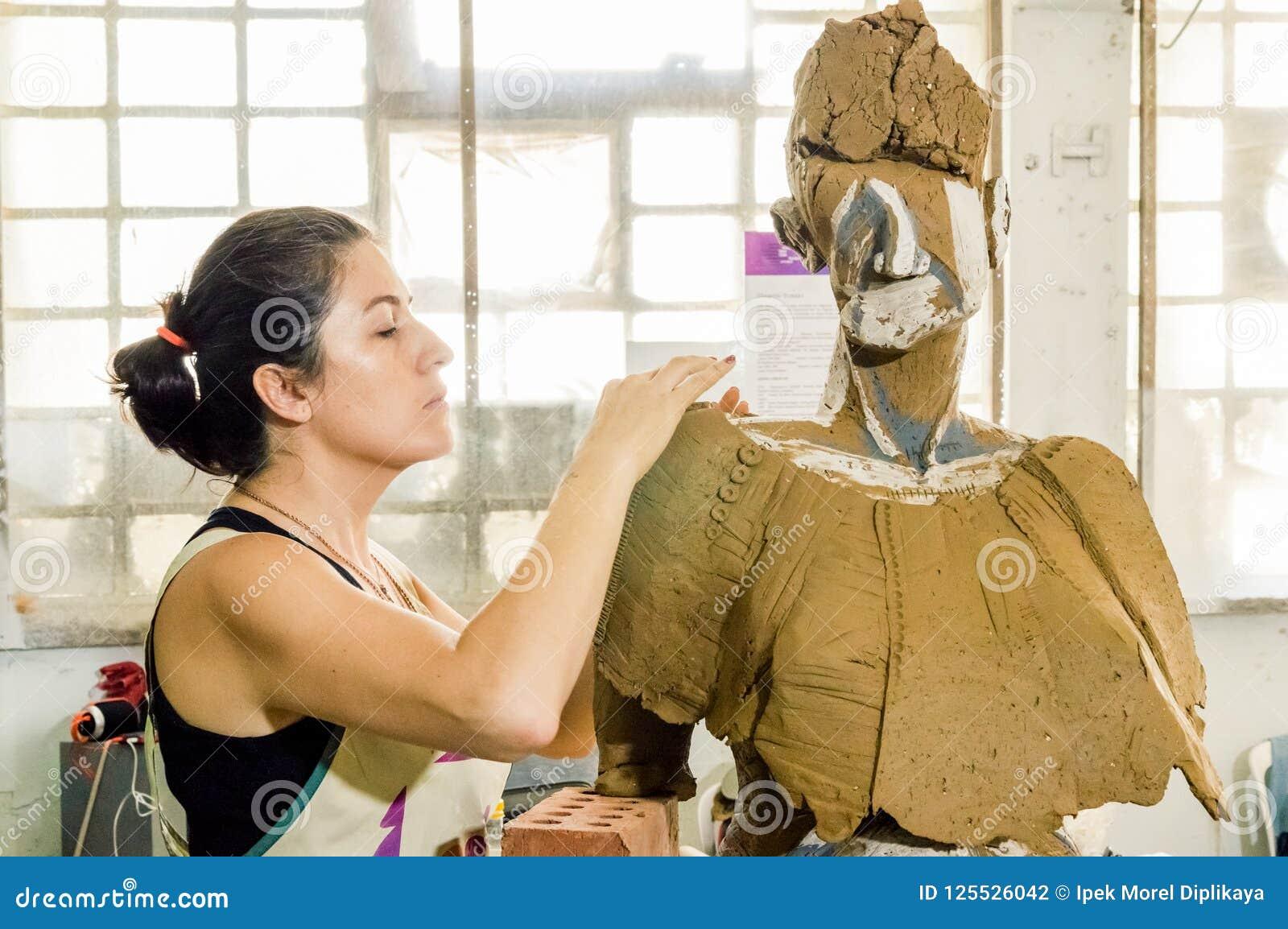 Härlig Caucasian konstnär som arbetar på hennes skulptur i en atelier