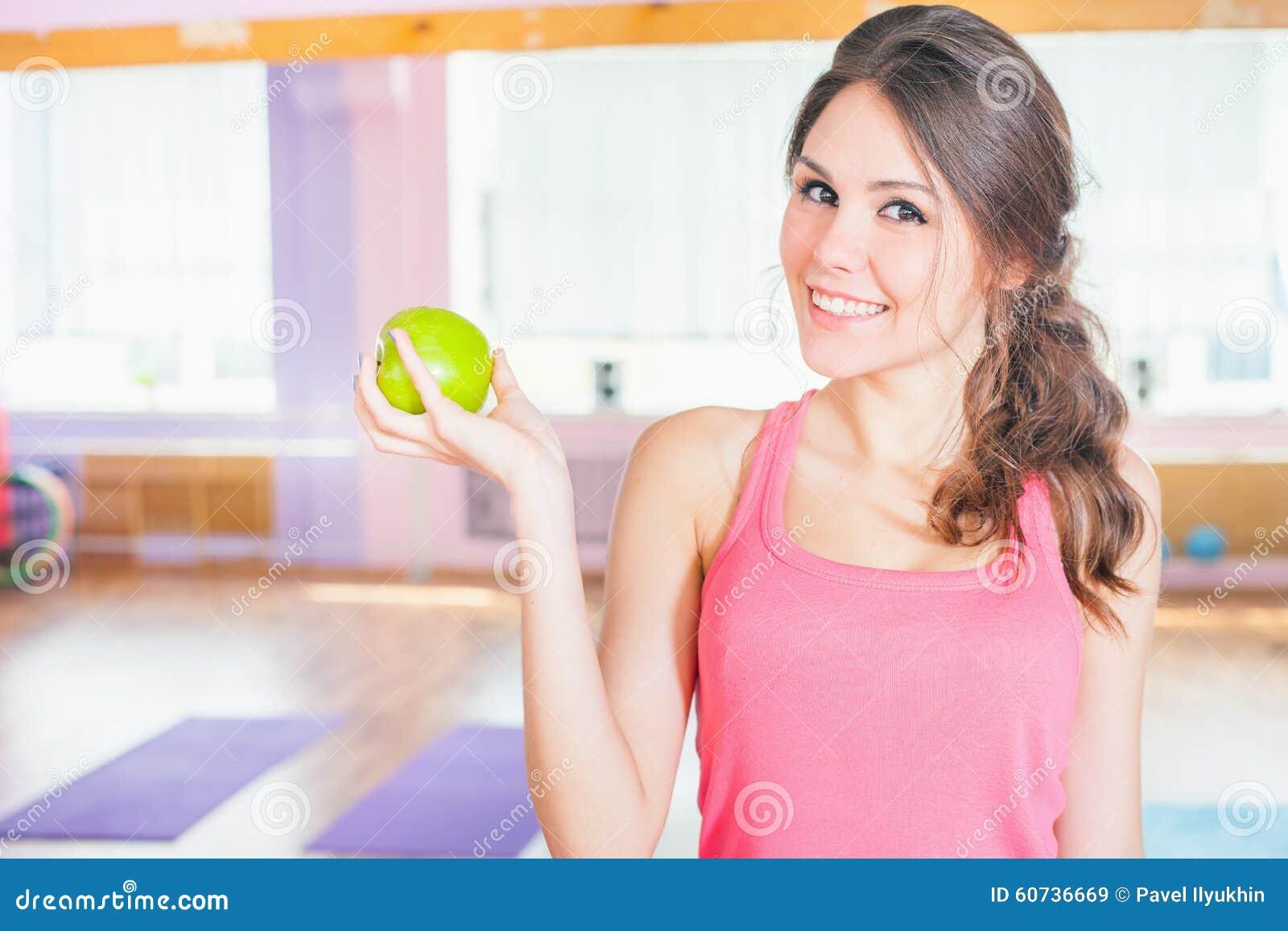 Härlig caucasian kvinna efter aple för gräsplan för konditionövningsinnehav