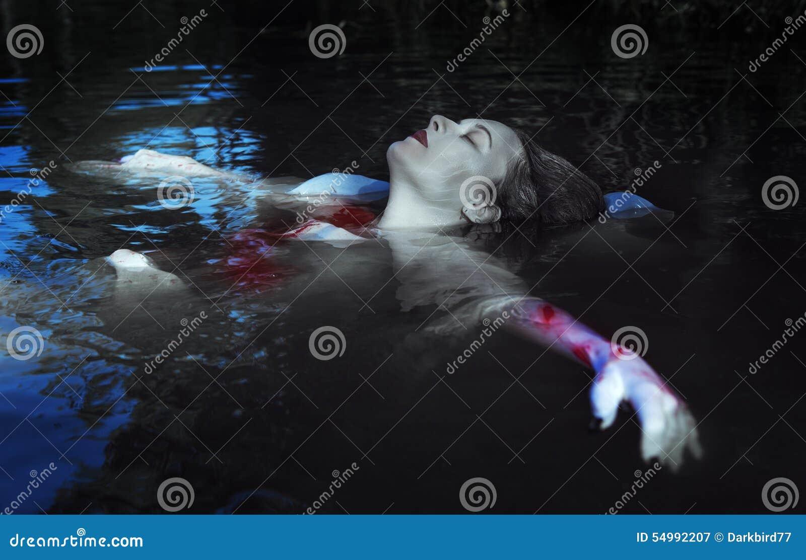 Härlig drunknad kvinna i den blodiga klänningen som ligger i vattnet