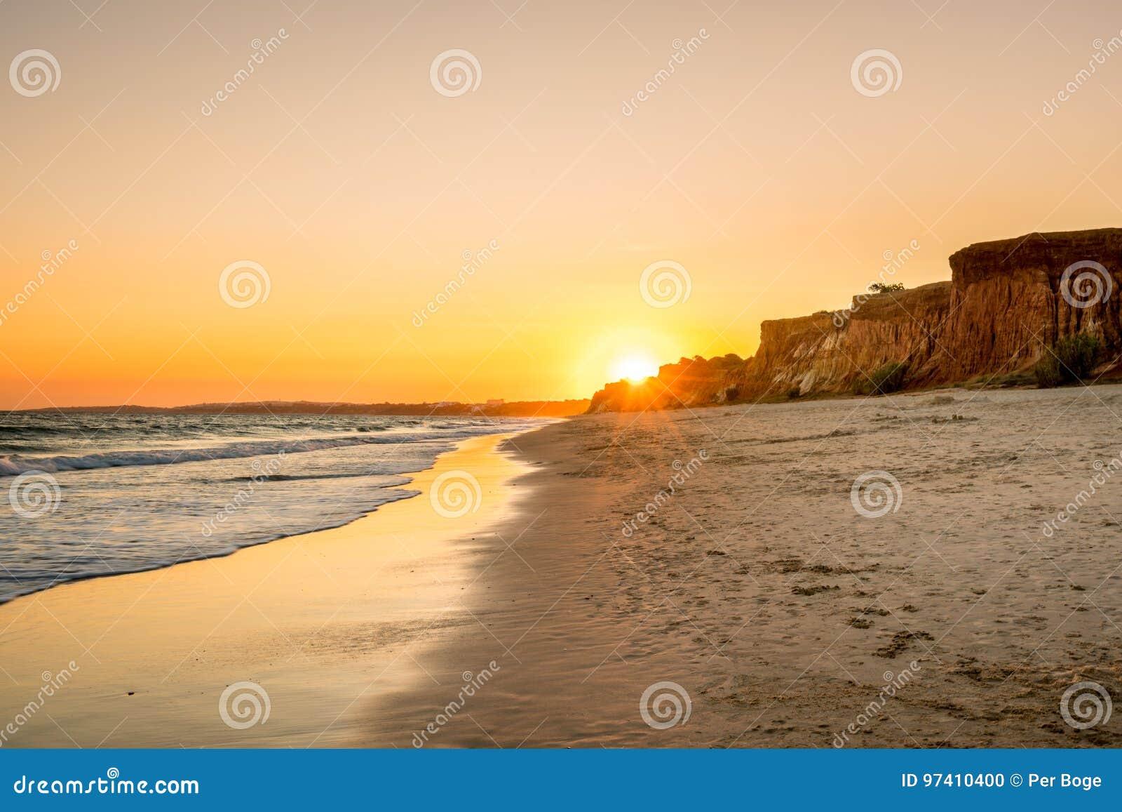 Härlig färgrik solnedgång i Algarve Portugal Fridsamt strandvatten och klippor