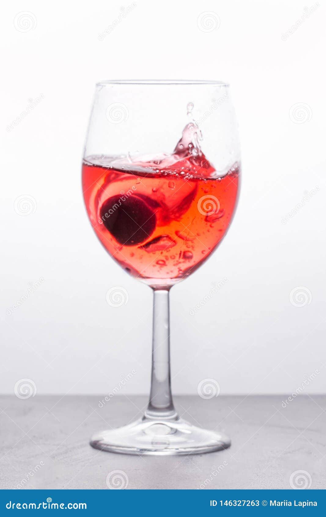 Härlig färgstänk i vinexponeringsglas med en rosa drink och en körsbärsröd berrie Ljus bakgrund