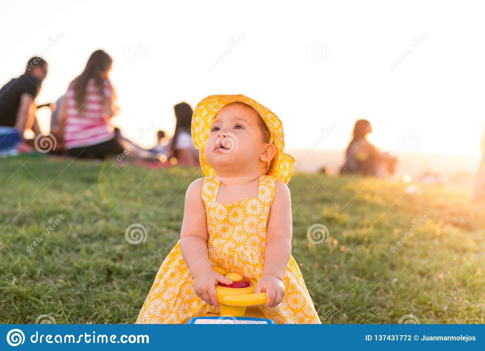 Härlig flicka för liten unge som utomhus sitter på en leksakbil