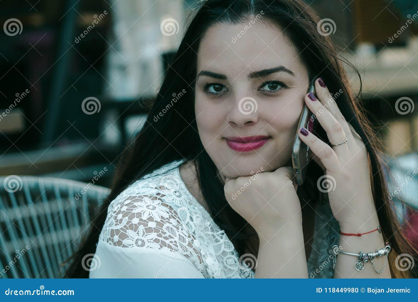 Härlig flicka för svart hår som talar på telefonen