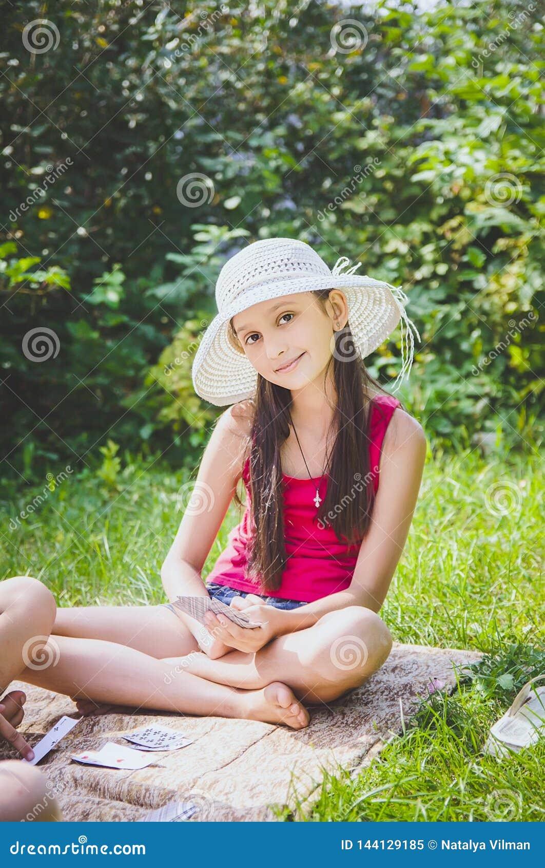 Härlig flicka 10 gamla år i en vit hatt som sitter på gräset i sommarträdgården