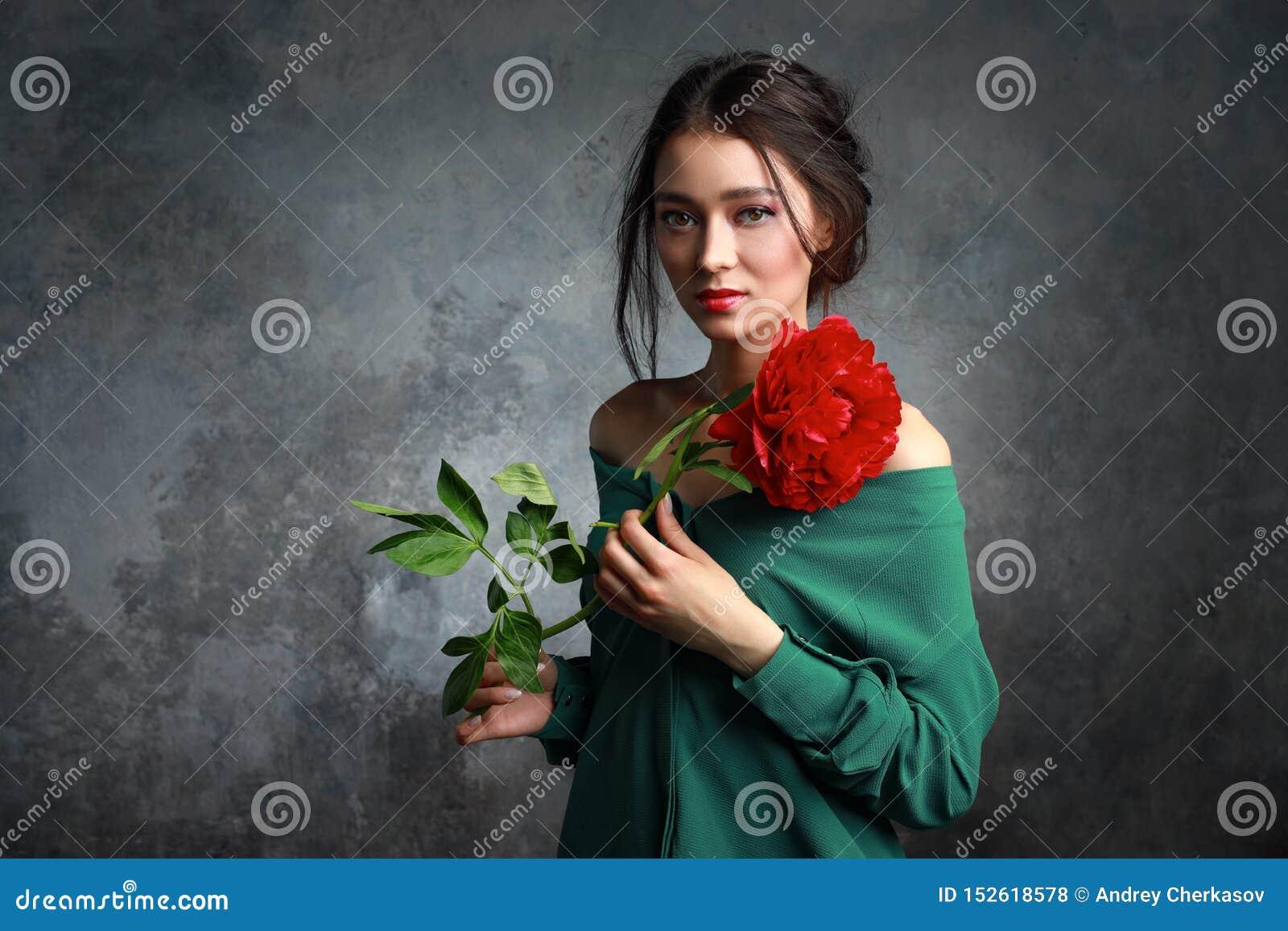 Härlig flicka i den gröna klänningen med blommapioner i händer på ett ljust - grå bakgrund Glad asiatisk kvinnlig modell som in p
