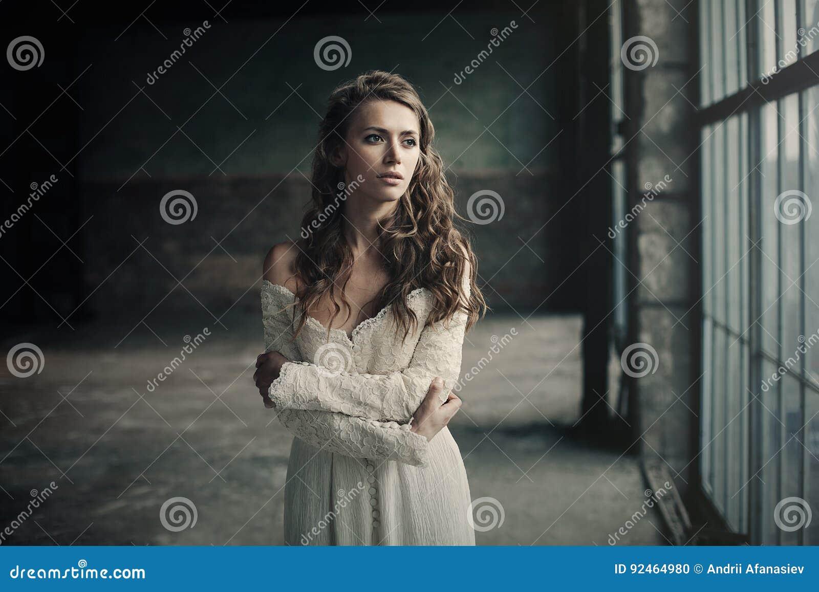 Härlig flicka in i den vita tappningklänningen med lockigt hår som poserar nära vindfönstret retro kvinna för klänning Bekymrad s